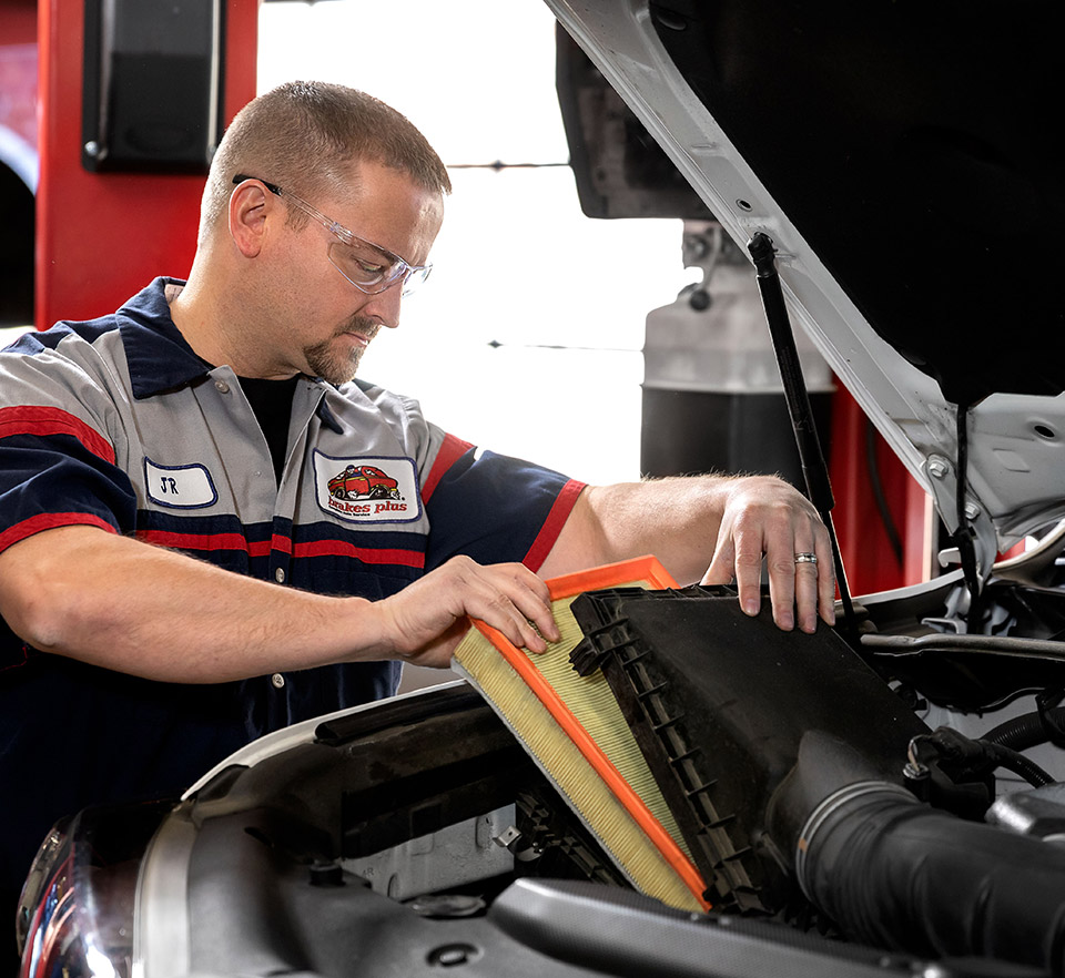 auto technician installing new air filter