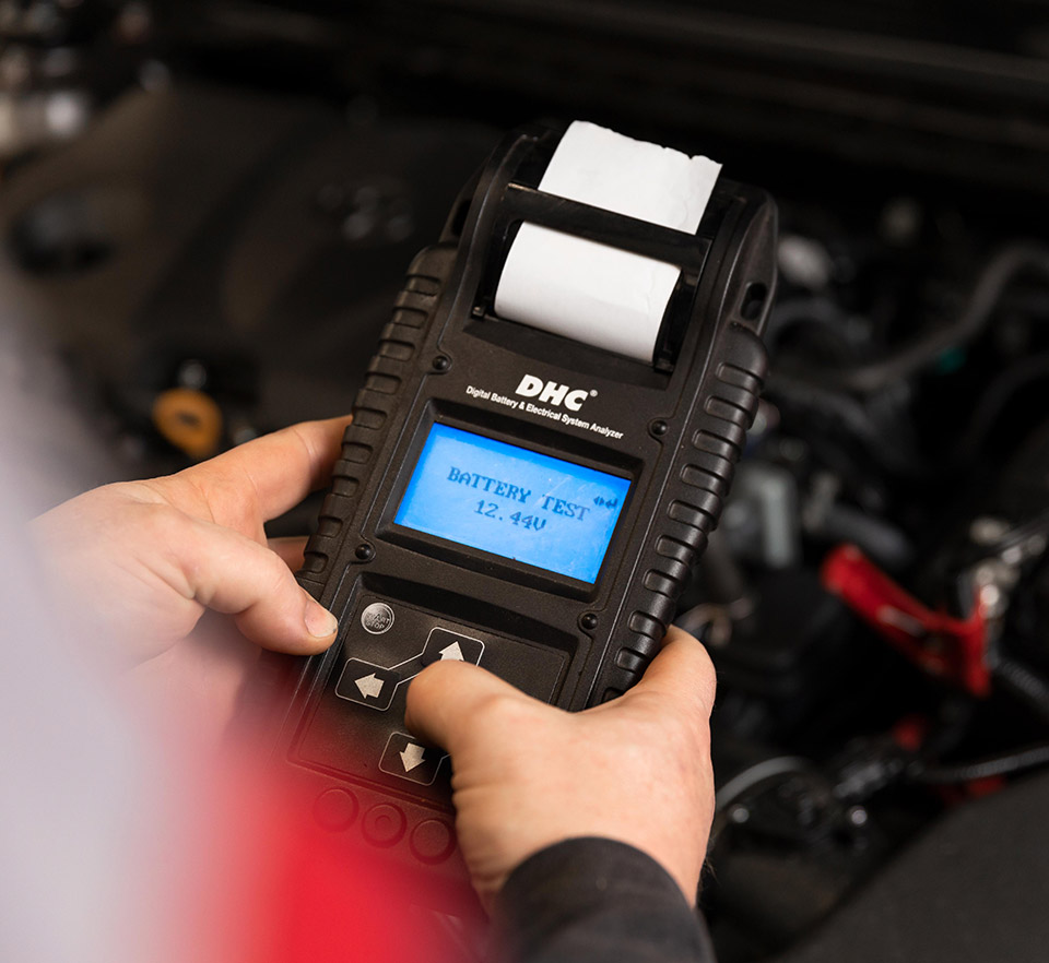 auto technician testing battery charge