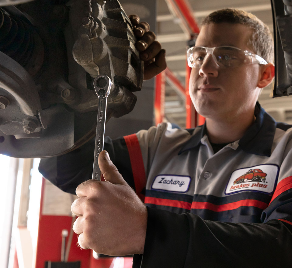 auto technician holding wrench