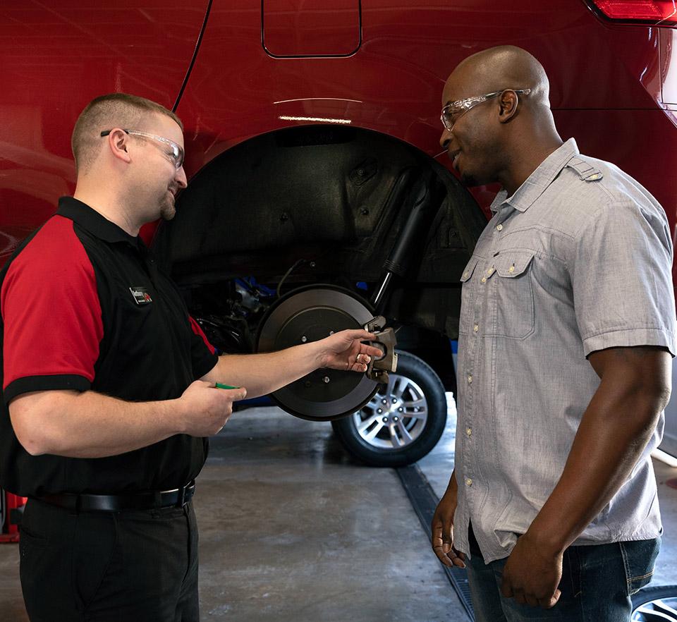 auto technician and customer beside car on lift