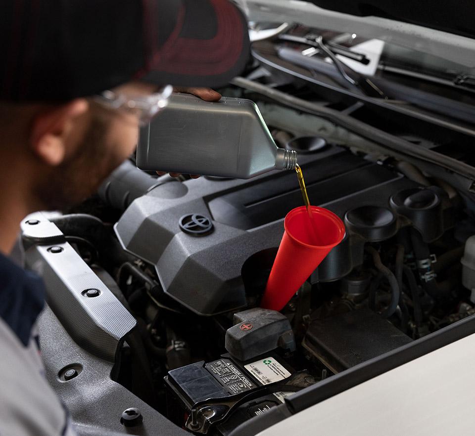 auto technician performing oil change