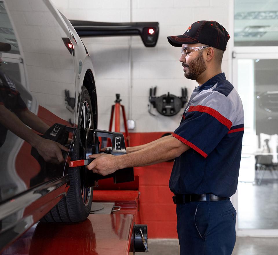auto technician inspecting tire