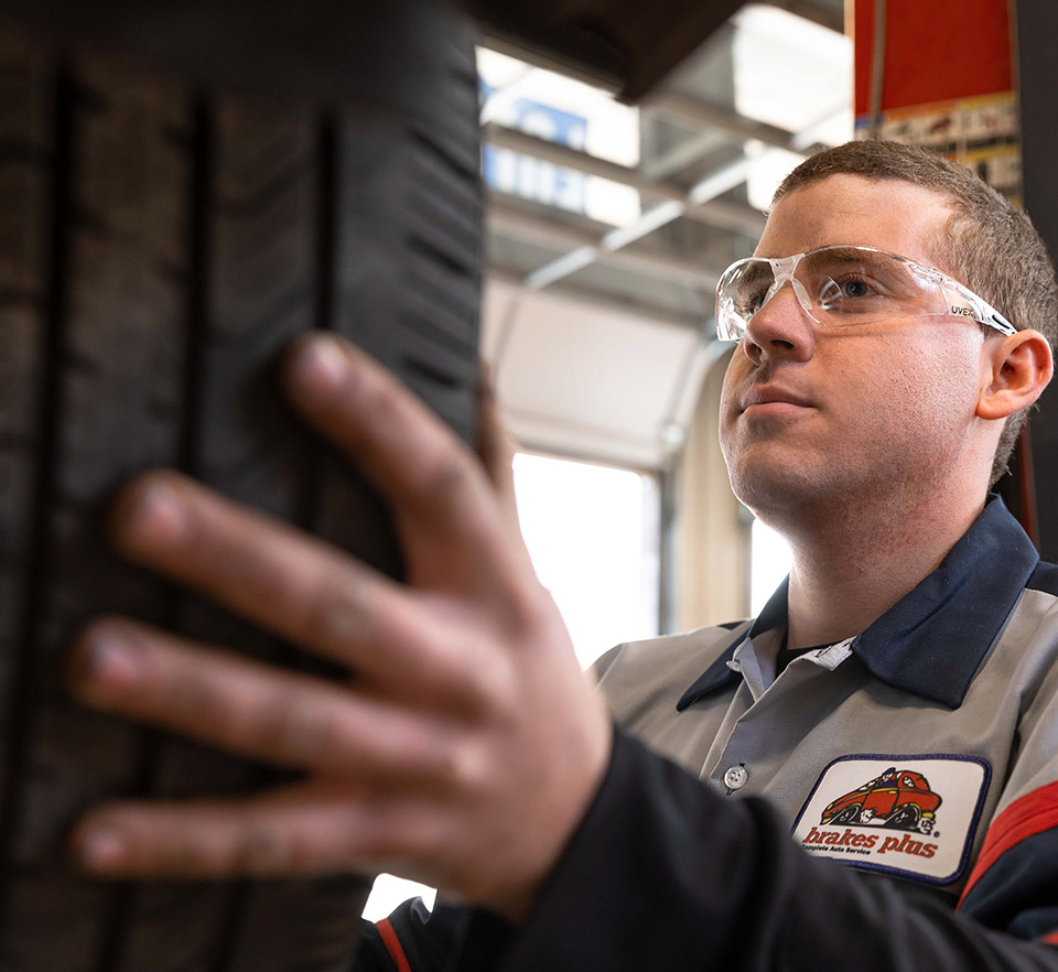 auto technician holding tire