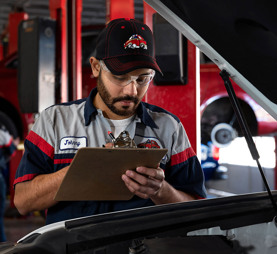 auto technician inspecting engine