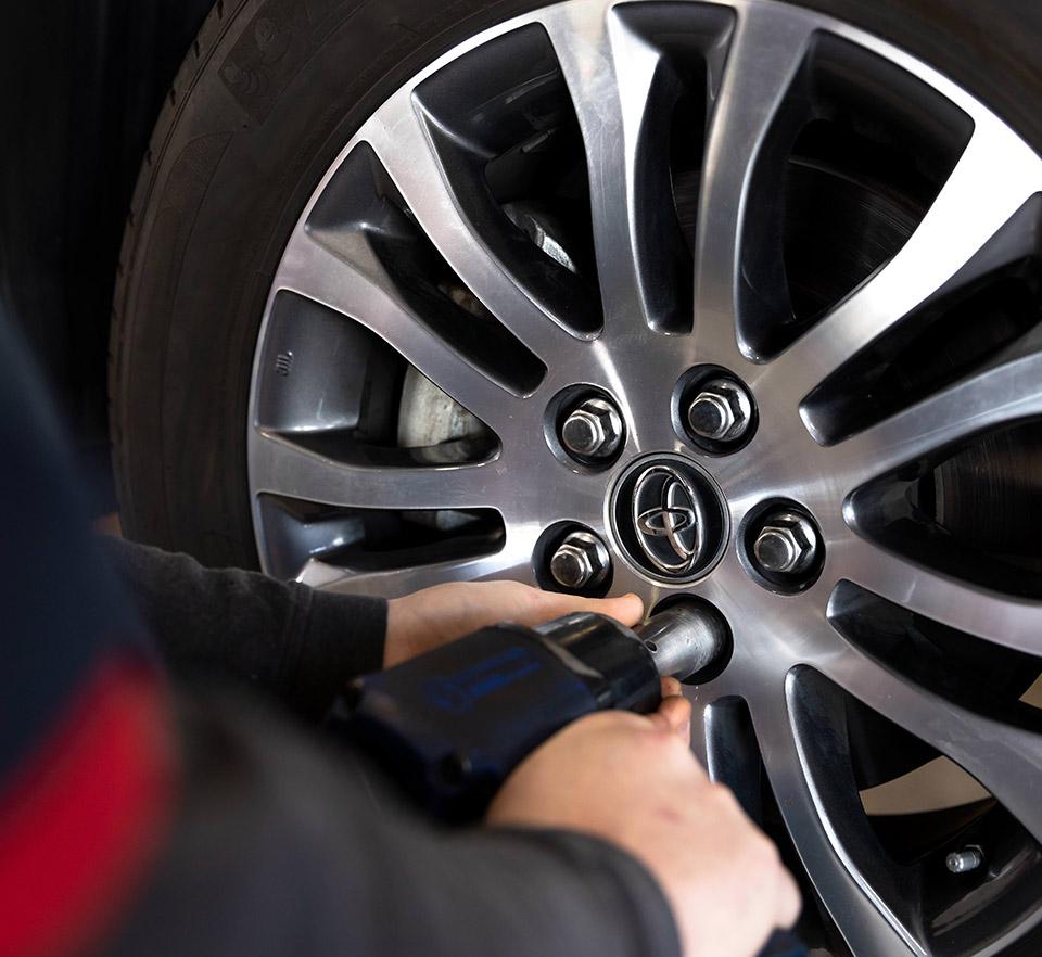 auto technician removing wheel bolts