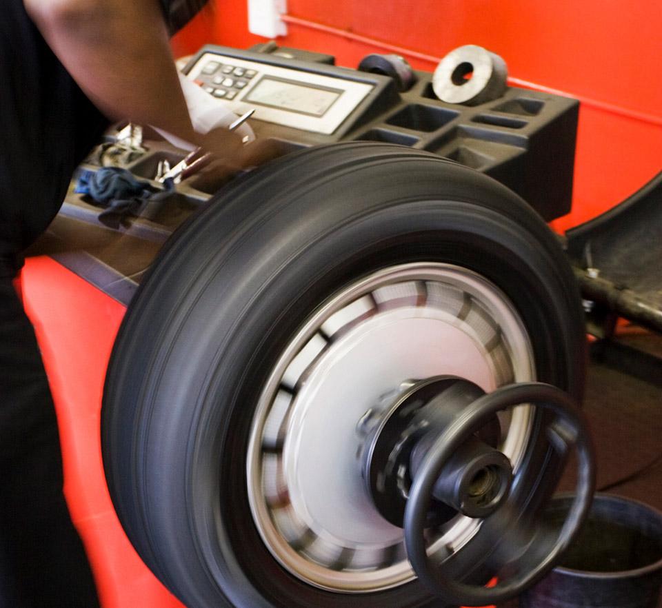 auto technician beside tire