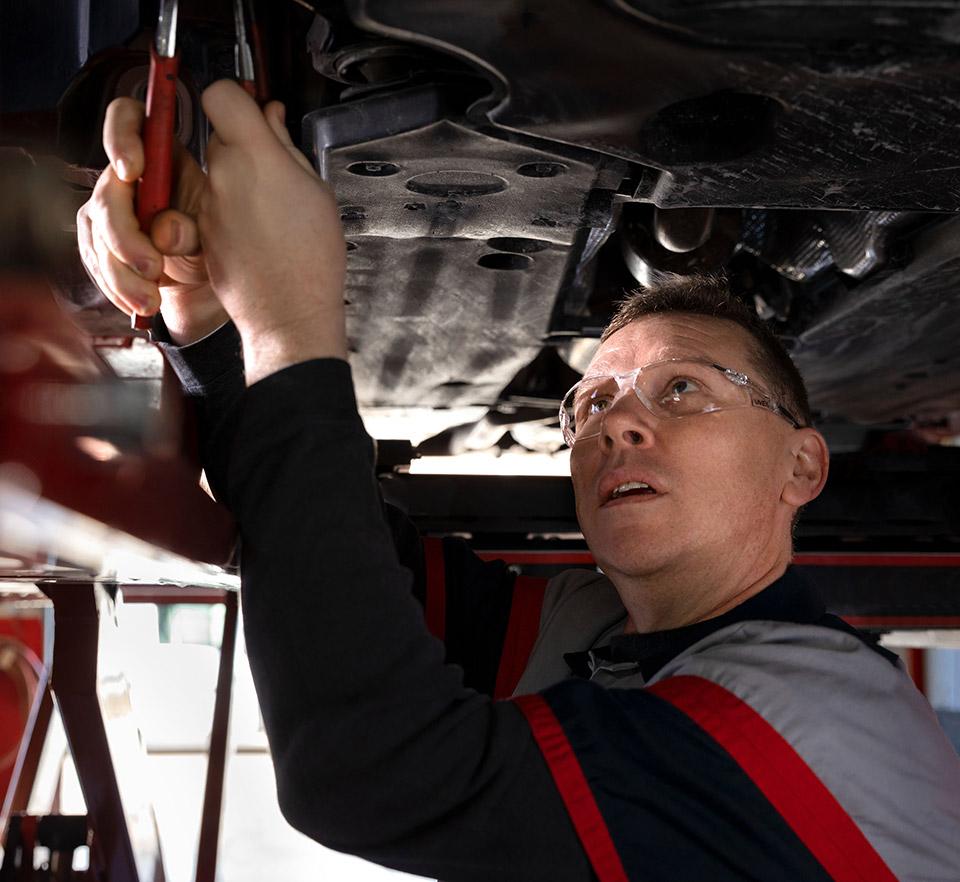auto technician working under car