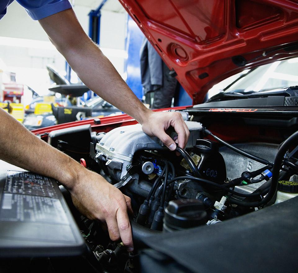 auto technician working under hood